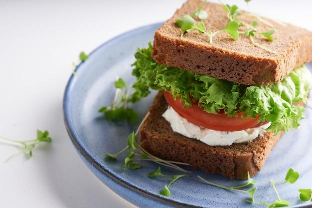 Здоровый бутерброд с безглютеновым хлебом, помидорами, листьями салата и пророщенными микрогринами, подается в тарелке на белом столе