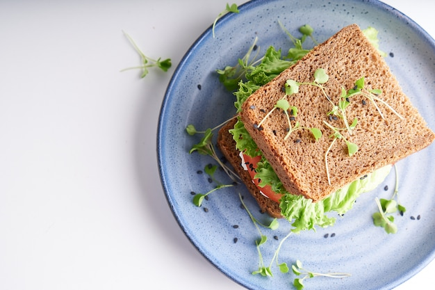 Здоровый бутерброд с безглютеновым хлебом, помидорами, листьями салата и пророщенными микрогринами, посыпанный семенами кунжута, подается в тарелке