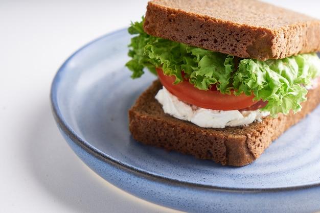 Здоровый бутерброд с безглютеновым хлебом, помидорами, листьями салата подается в тарелке на белом столе