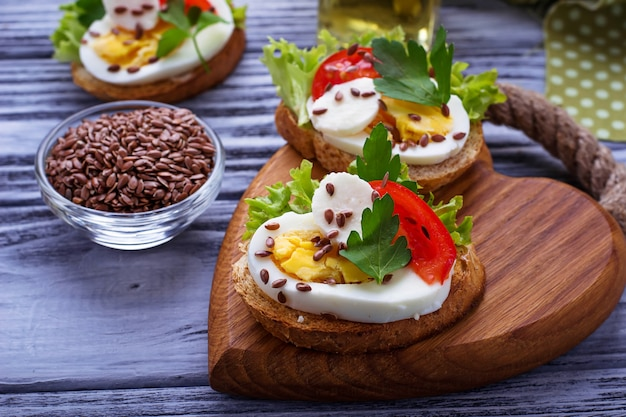 Healthy sandwich with mozzarella, tomato, eggs and flax-seed