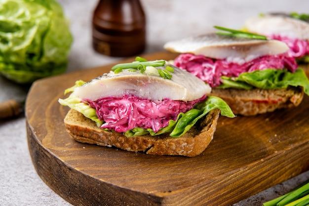 소금에 절인 청어, 비트, 그린 샐러드를 곁들인 건강 샌드위치