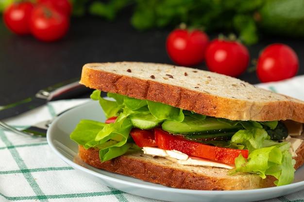Healthy sandwich with vegetables on dark wooden background