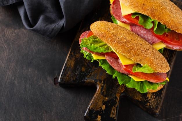 素朴な木製のスタンドにふすまパン、チーズ、グリーンレタス、トマト、スライスしたサラミを添えたヘルシーなサンドイッチ。朝食のコンセプト。上面図