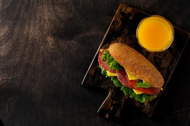 素朴な木製のスタンドにふすまパン、チーズ、レタス、トマト、スライスしたサラミと絞りたてのオレンジジュースを添えたヘルシーなサンドイッチ。朝食のコンセプト。上面図。