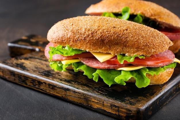 素朴な木製のスタンドにふすまパン、チーズ、レタス、トマト、スライスしたサラミを添えたヘルシーなサンドイッチ。朝食のコンセプト。上面図。