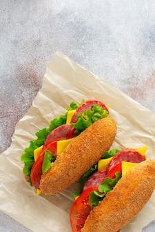 밀기울 빵, 녹색 양상추, 치즈, 빨간 토마토, 얇게 썬 살라미 소시지를 양피지와 소박한 나무 스탠드에 넣은 건강한 샌드위치. 아침 식사 개념입니다. 평면도