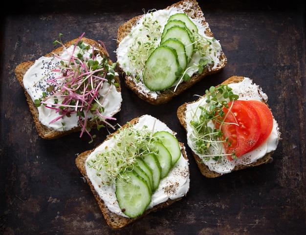 クリームチーズ、マイクログリーン、トマト、キュウリのヘルシーなサンドイッチ。健康的な食事、ダイエット食品、ビーガンフード