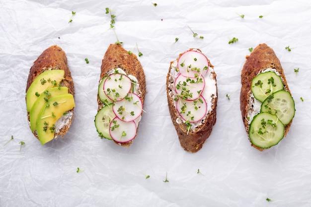 Healthy sandwiches with grain bread, ricotta, avocado, cucumber, radish and mustard micro greens.