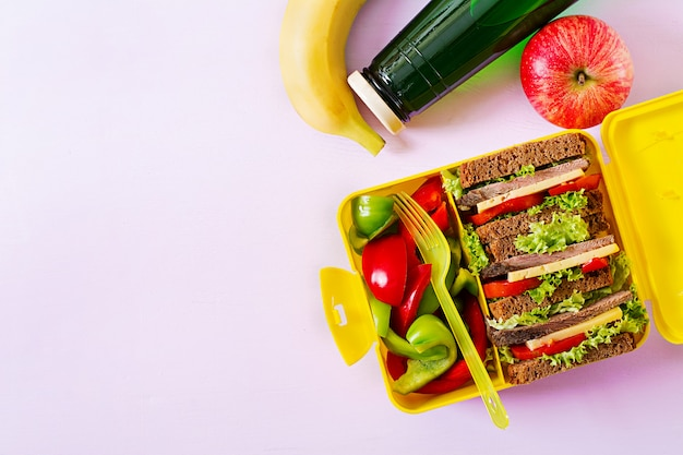 ビーフサンドイッチと新鮮な野菜、ボトル入りの水とピンクのテーブルの果物と健康的な学校のランチボックス。上面図。フラットレイ