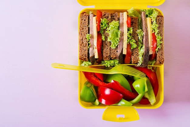 Healthy school lunch box with beef sandwich and fresh vegetables  on pink table. top view. flat lay