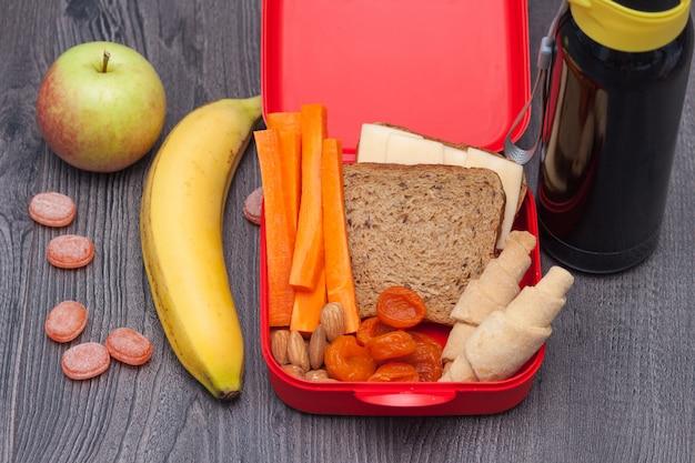 Здоровый школьный обед с сэндвичем, яблоком, бананом, миндалем, сухофруктами, водой, натуральными конфетами, морковью, печеньем.