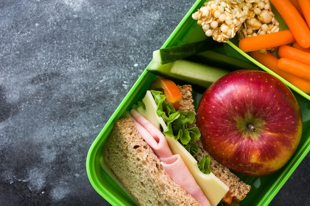 Healthy school lunch box with sandwich, vegetables and fruit on black stone