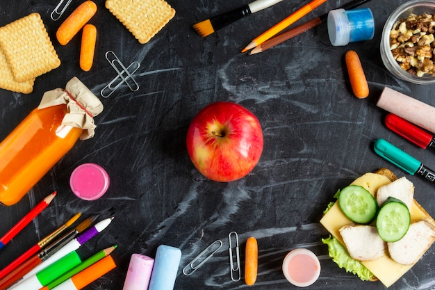 Healthy school lunch concept. red apple, sandwich, juice and stationery on blackboard