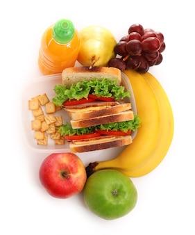 흰색으로 분리된 샌드위치, 과일, 주스가 포함된 건강한 학교 점심
