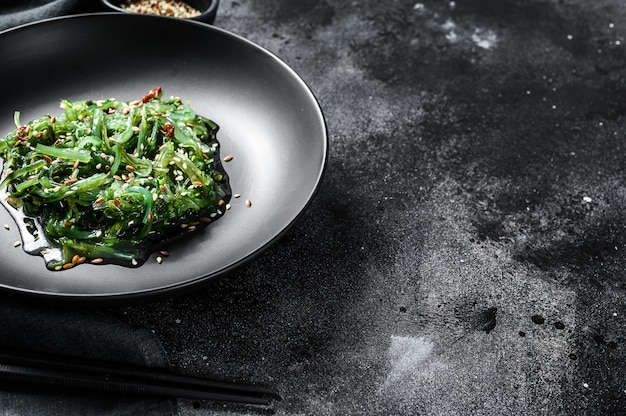 Healthy seaweed chuka salad with greens. black background. top view. copy space