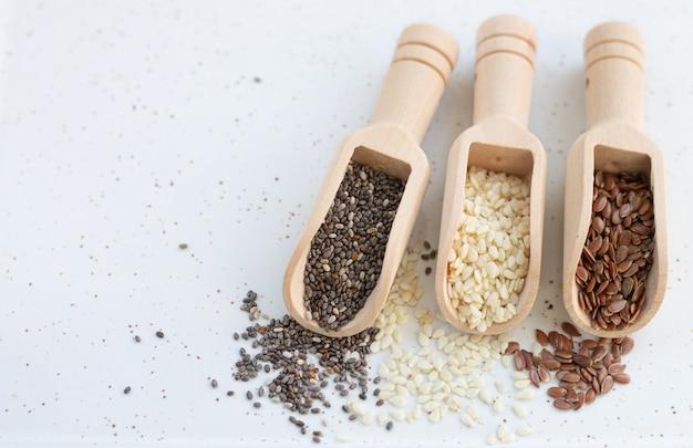 Концепция здоровых семян. деревянные совки с белым кунжутом, семенами льна и чиа