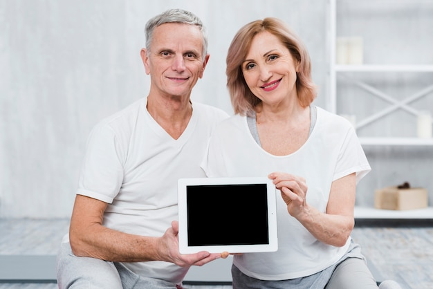 Healthy senior couple looking at camera holding digital tablet with black screen