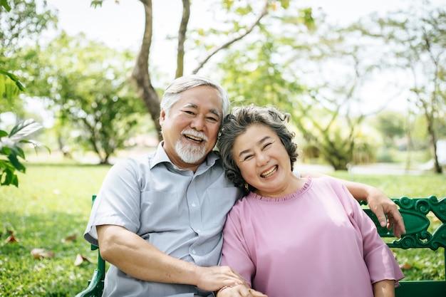 Здоровая пара старшего отдыха расслабляющий на скамейке в парке