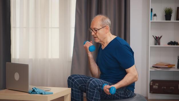 オンラインフィットネスレッスン後の健康な年配の男性のトレーニング。老人年金受給者が自宅でヘルスケアスポーツを健康的に訓練し、高齢者でフィットネス活動を行う