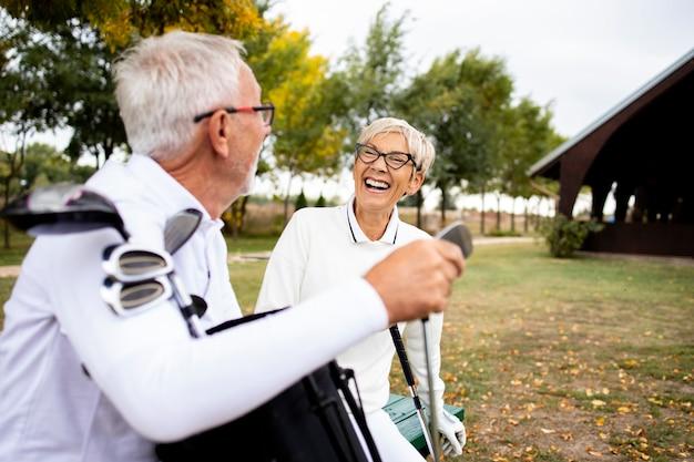Здоровые старшие люди наслаждаются временем отдыха и смеются вместе на тренировке в гольф.