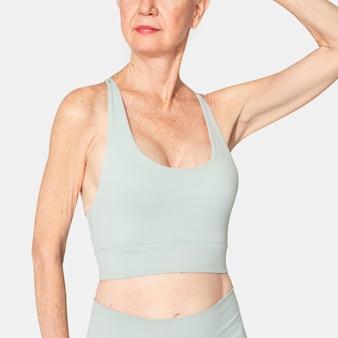 Здоровая старшая женщина в мятно-зеленом спортивном бюстгальтере и леггинсах