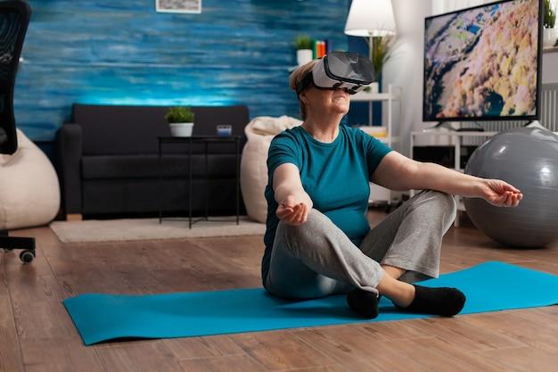 Здоровая старшая женщина с помощью гарнитуры виртуальной реальности медитирует, сидя в позе лотоса