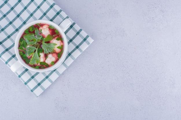 大理石の背景に折りたたまれたテーブルクロスの上の小さなボウルにカリフラワーのスープの健康的なサービング。高品質の写真