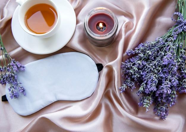 健康的な睡眠の概念。シルクの背景にラベンダーの花束、睡眠マスク、キャンドル