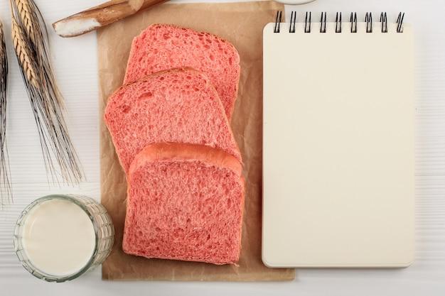 요리 책, 텍스트 또는 광고용 조리법을 위한 빈 책 옆에 있는 건강한 분홍 빵. 2021년 새해 다이어트 계획에 대한 개념. 상위 뷰
