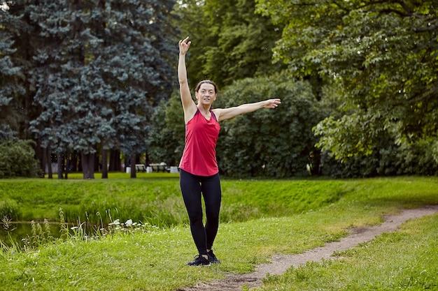건강한 슬림 여성은 낮에는 연못 근처의 공공 공원에서 야외에서 신체 운동을하고 있습니다.