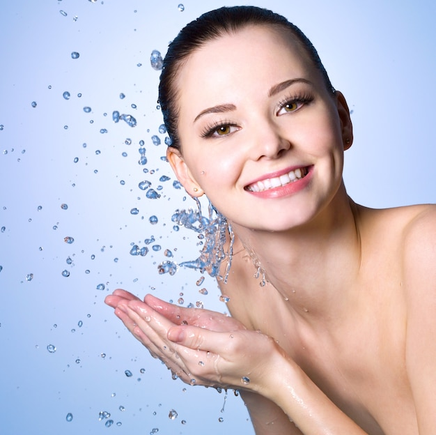Healthy smiling  woman washing her face with clean water