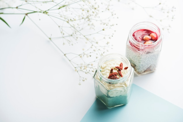 Healthy smoothie jars and gypsophila on white background