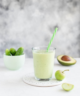 Healthy smoothie with avocado, cucumber and apple in a glass with a straw