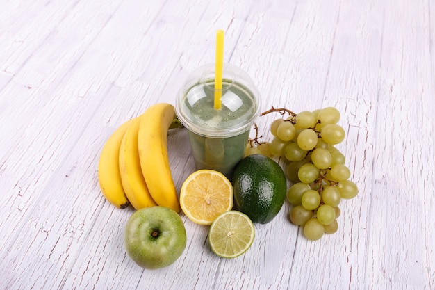 バナナ、ライム、ブドウの健康なスムージーがテーブルに横たわっています
