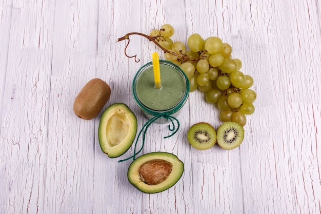 Healthy smoothie with grape,avocado and kiwi lie on the table