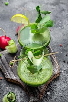 ケールグリーンの新鮮なエンドウ豆、キュウリ、ほうれん草、ライムの緑の葉を使ったヘルシーなスムージー。健康的なデトックスドリンク。