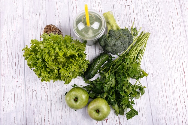 Здоровый коктейль с зелеными овощами и фруктами лежит на столе