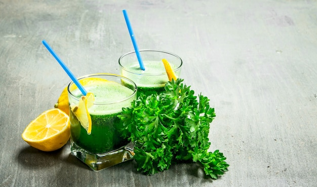Healthy smoothie with lemon and parsley on rustic background