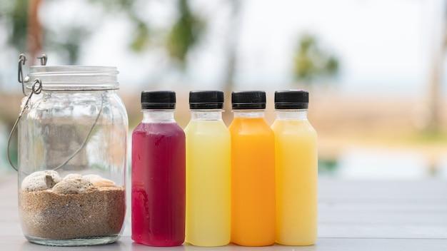健康的なスムージーの果物と野菜のジュースをボトルに入れ、砂をボトルに入れます Premium写真