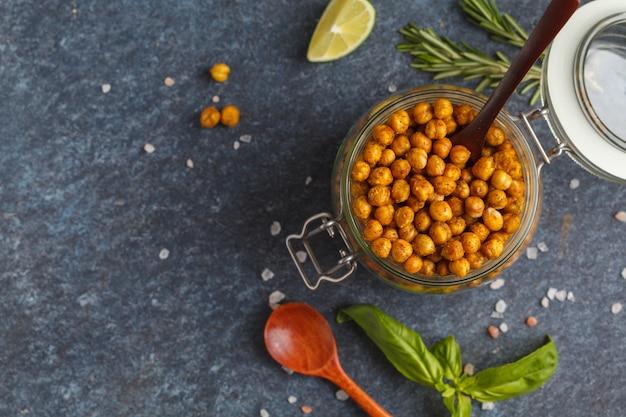健康的なスナック-ガラスの瓶、上面図、コピースペースで焼きスパイシーなひよこ豆。健康的なビーガンフードのコンセプトです。