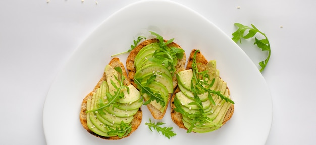 Healthy snack concept. toasts with avocado, shrimps and arugula on white background. top view, flat lay.