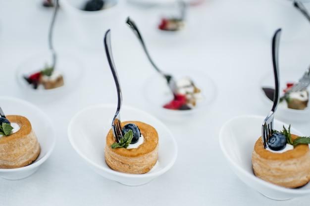 ラズベリー、ブルーベリー、イチゴの小さなボウルと健康的なスナック食品
