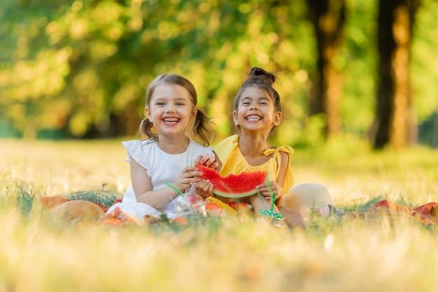 子供のための健康的なスナック小さな女の子がスイカのスライスを噛んで森で遊んでいます