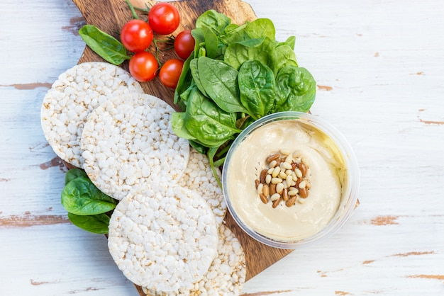 Healthy snack from rice cakes with hummus, spinach and tomatoes