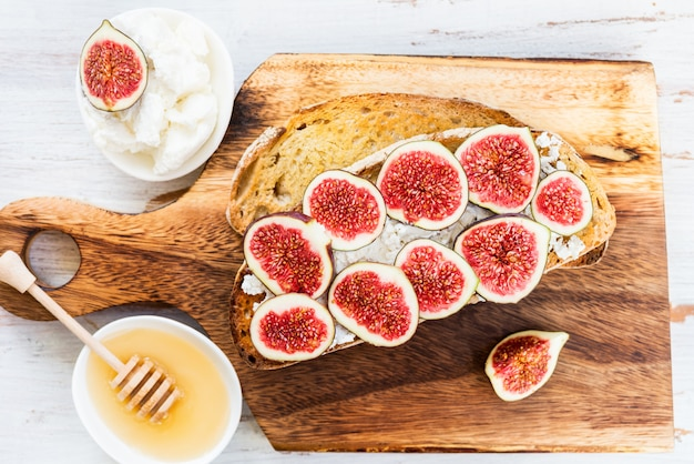 Healthy snack from sourdough bread toasts, figs and ricotta chee