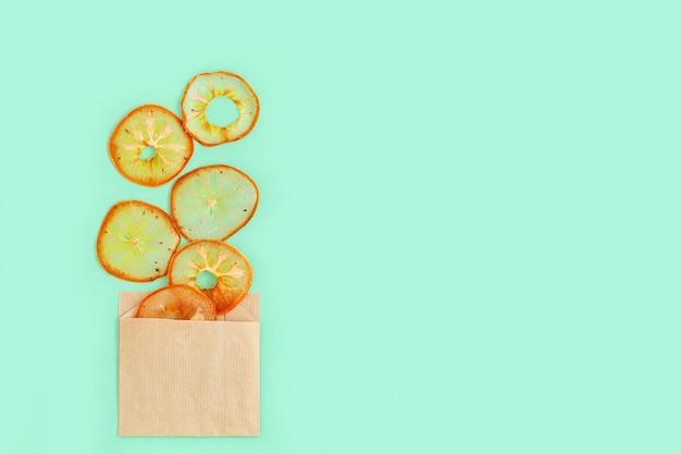 健康的なスナックミント色の背景に柿の自家製ドライフルーツチップス