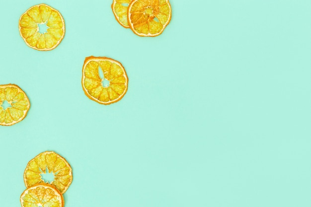 Healthy snack. homemade dehydrated fruit chips of tangerine. dry tangerine on paper background. diet food concept. top view and copy space.