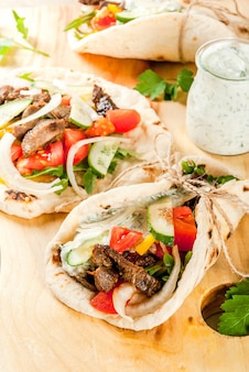Healthy snack, lunch. traditional greek wrapped sandwich gyros - tortillas, bread pita with a filling of vegetables, beef meat and sauce tzatziki