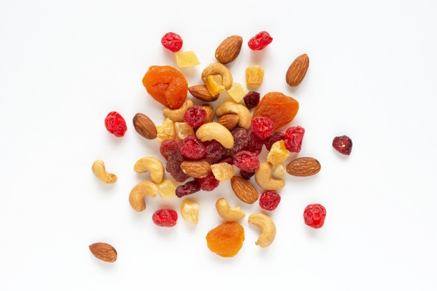 Healthy snack: mixed nuts and dried fruits on white background from above.