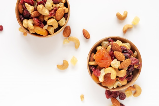 Healthy snack: mixed nuts and dried fruits in wooden bowl on  white background from above.